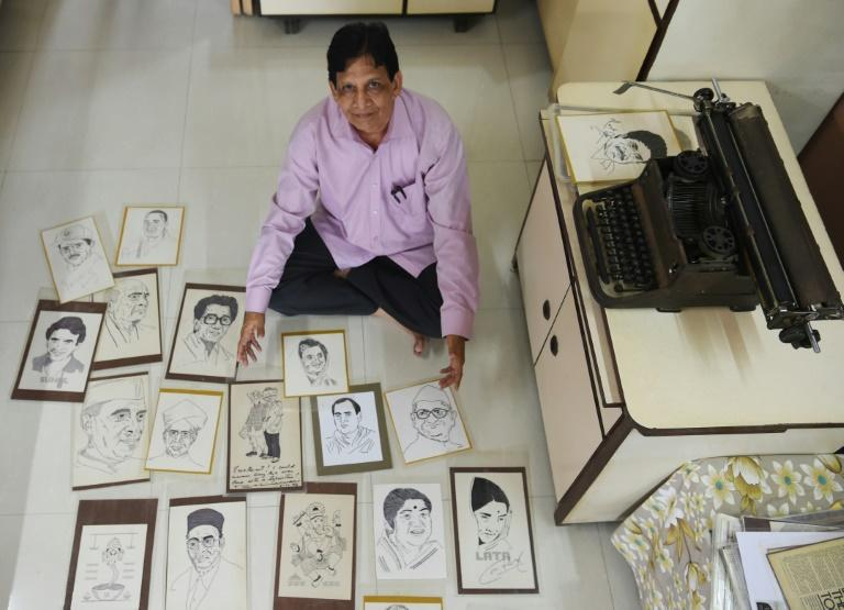 Indian artist Chandrakant Bhide poses with artwork showing portraits of public figures and deities that he created using a typewriter