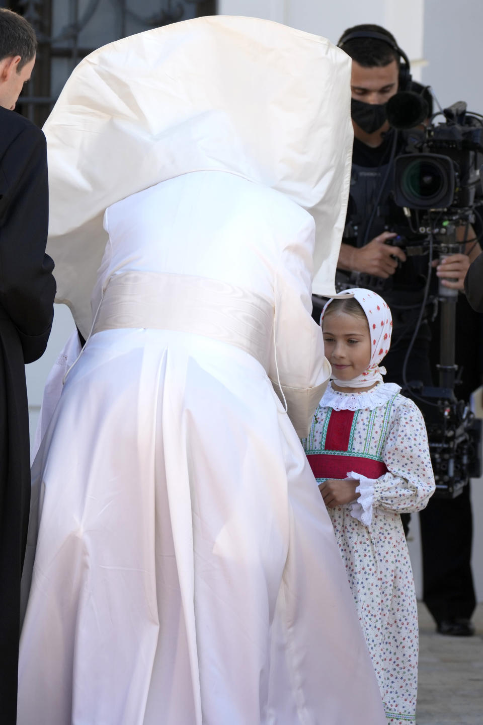 Pope Francis' mantle is blown by the wind as he greets a child during a welcoming ceremony at the presidential palace in Bratislava, Slovakia, Monday, Sept. 13, 2021. Francis is on a four-day visit to Central Europe, in Hungary and Slovakia, in his first big international outing since undergoing intestinal surgery in July. (AP Photo/Gregorio Borgia)