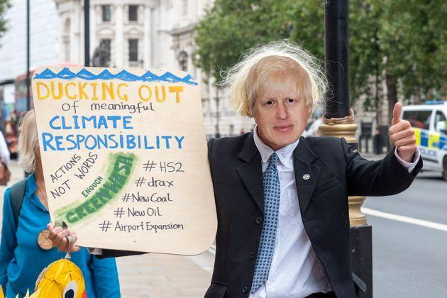 Extinction Rebellion protesters with a Boris Johnson mask (Photo: SOPA Images via Getty Images)