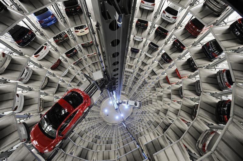 """A Volkswagen """"Beetle"""" (R) and an """"UP!"""" are pictured in a delivery tower at the company's headquarter in Wolfsburg."""