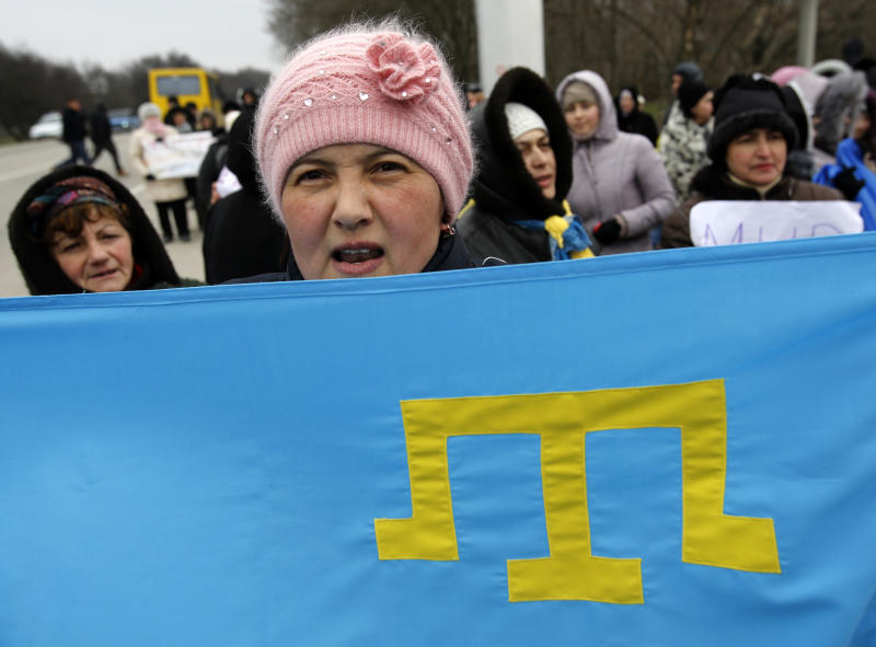 "Crimean Tatars shout slogans and hold Tatar flag during the pro Ukraine rally in Simferopol, Crimea, Ukraine, Monday, March 10, 2014. Russian President Vladimir Putin on Sunday defended the separatist drive in the disputed Crimean Peninsula as in keeping with international law, but Ukraine's prime minister vowed not to relinquish ""a single centimeter"" of his country's territory. The local parliament in Crimea has scheduled a referendum for next Sunday. (AP Photo/Darko Vojinovic)"