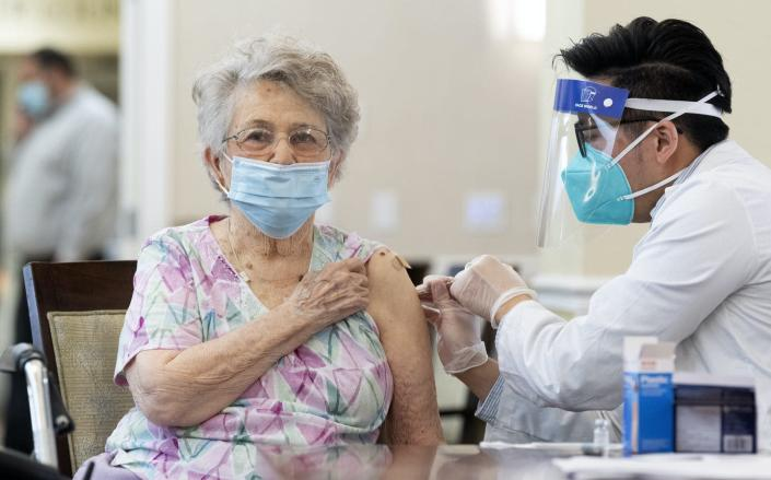 """<span class=""""caption"""">By mid-January, only about a quarter of the COVID-19 vaccines distributed for U.S. nursing homes through the federal program had reached people's arms.</span> <span class=""""attribution""""><a class=""""link rapid-noclick-resp"""" href=""""https://www.gettyimages.com/detail/news-photo/pharmacist-gives-the-pfizer-biontech-covid-19-vaccine-to-a-news-photo/1295381204"""" rel=""""nofollow noopener"""" target=""""_blank"""" data-ylk=""""slk:Paul Bersebach/MediaNews Group/Orange County Register via Getty Images""""> Paul Bersebach/MediaNews Group/Orange County Register via Getty Images</a></span>"""
