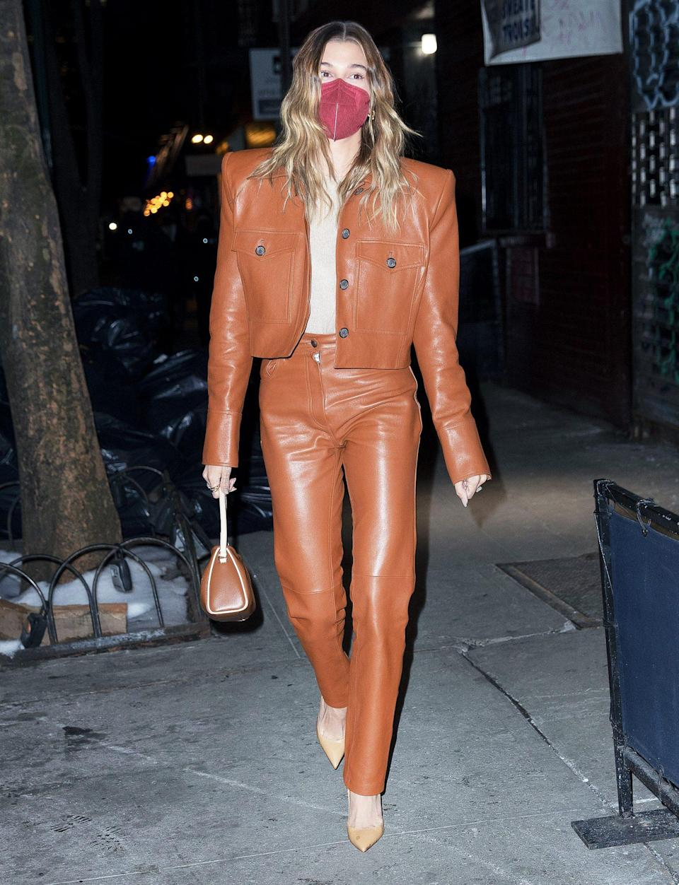 <p>Hailey Bieber looks sharp in a two-piece leather suit as she heads to dinner with singer Justine Skye at Carbone in N.Y.C. on Sunday.</p>