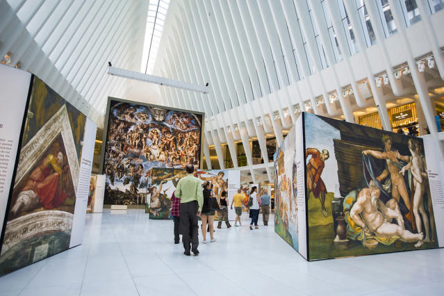 "<p>Guests walk through the ""Up Close: Michelangelo's Sistine Chapel"" re-creation exhibit at the Oculus at Westfield World Trade Center in New York. The exhibit features 34 reproductions, including ""The Creation of Adam"" and ""The Last Judgement."" (AP Photo/Michael Noble Jr.) </p>"