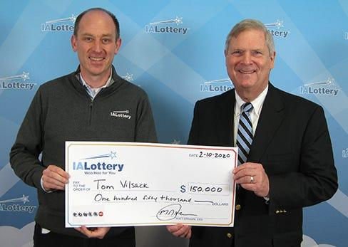 Iowa Lottery CEO Matt Strawn, left, and Tom Vilsack show off Vilsack's $150,000 winnings. Vilsack, the former Iowa governor, claimed the $150,000 Powerball prize Feb. 10 at Iowa Lottery headquarters in Clive.