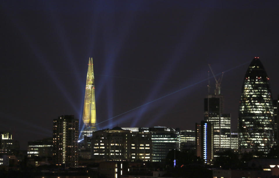 A laser beam touches the Gherkin from the Shard during the laser and searchlight show which marks the completion of the exterior of the Shard building in central London July 5, 2012. The 310-metre (1,016-feet) building, the tallest in western Europe, fired 12 lasers and 30 searchlights from the top of the Shard to 15 London skyscrapers including the Gherkin and the Canary Wharf. REUTERS/Olivia Harris (BRITAIN - Tags: SOCIETY BUSINESS CONSTRUCTION CITYSPACE)