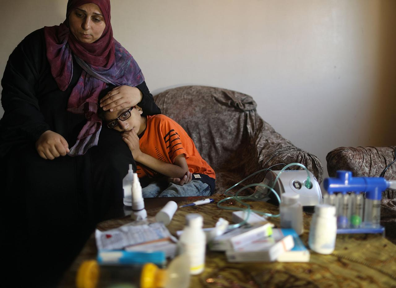 <p>Palestinian boy Mohammad Shanty, who suffers from cystic fibrosis, sits next to his mother after receiving oxygen therapy during a power cut in their family house, which is equipped with a backup battery-powered system, in Gaza City, July 2, 2017. (Photo: Mohammed Salem/Reuters) </p>