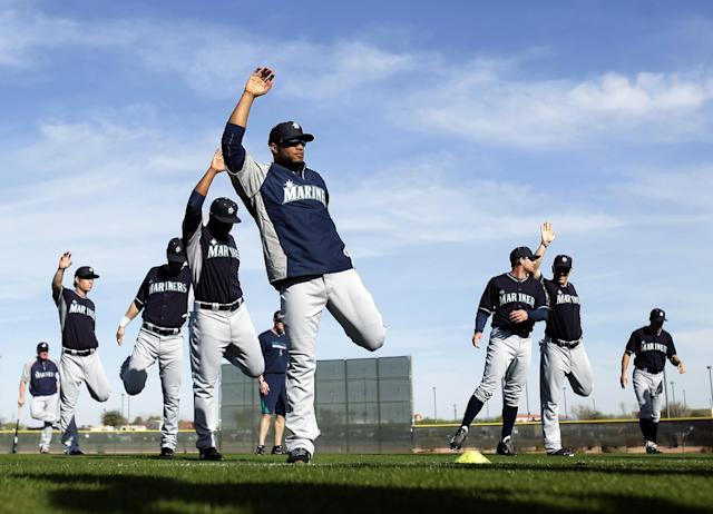 Seattle Mariners second baseman Robinson Cano, front, stretches with his teammates before baseball spring training, Tuesday, Feb. 18, 2014, in Peoria, Ariz. (AP Photo/Rick Scuteri)