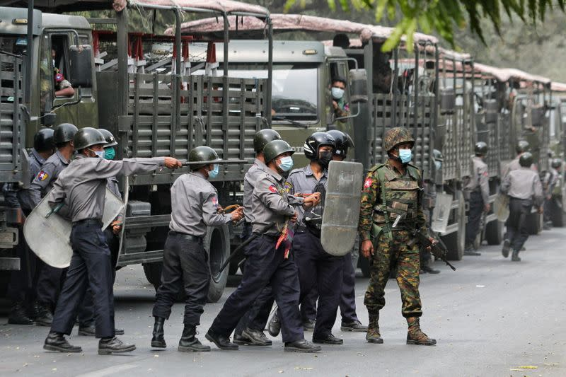Police and soldiers are seen during a protests against the military coup, in Mandalay