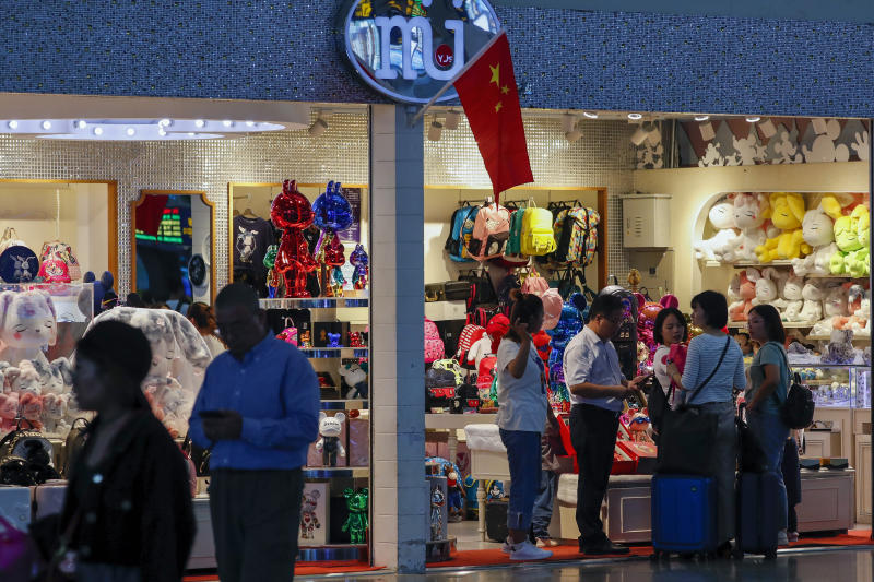 Passengers shop at the Shanghai Disney flagship store at the Hongqiao Railway Station in Shanghai, China, Monday, Oct. 14, 2019. China's trade with the United States fell by double digits again in September amid a tariff war that threatens to tip the global economy into recession. (AP Photo/Andy Wong)
