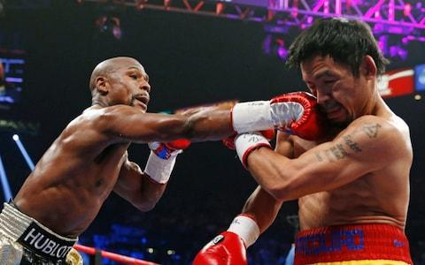 Floyd Mayweather Jr., left, connects with a right to the head of Manny Pacquiao, from the Philippines, during their welterweight title fight in Las Vegas - Credit: AP