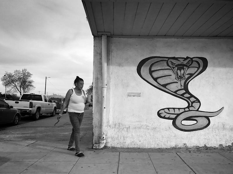 A woman walks near a street mural in Mendota, Calif. The rural community has long been the base for migrant farm laborers who come to work in the Central Valley, but farmers say there is a labor shortage this year amid Trump's immigration threats (Photo: Holly Bailey/Yahoo News)