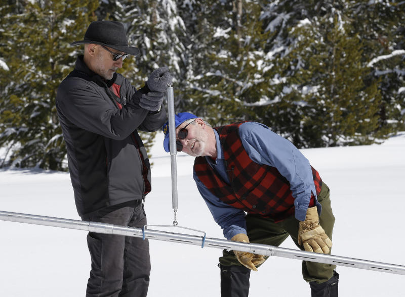 Frank Gehrke, right, chief of the California Cooperative Snow Surveys Program for the Department of Water Resources, checks the weight of the snowpack on a scale held by Armando Quintero, chairman of the California Water Commission, during the third manual snow survey of the season at Phillips Station, Wednesday, March 1,2017, near Echo Summit, Calif. The survey showed the snowpack at 179 percent of normal for this location at this time of year.The state's electronic snow monitors say the Sierra Nevada snowpack is at 185 percent of normal. (AP Photo/Rich Pedroncelli)