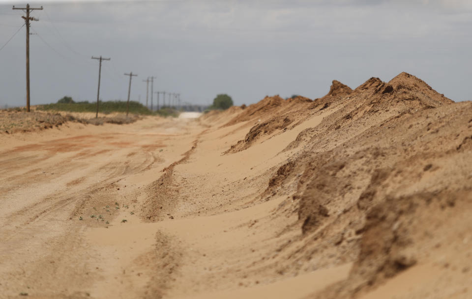 """Sand that blew off farmers' fields is piled up in a ditch outside Lingo, N.M., near the Texas-New Mexico border on Tuesday, May 18, 2021. The U.S. Department of Agriculture is encouraging farmers in a """"Dust Bowl zone"""" that includes parts of Texas, New Mexico, Oklahoma, Kansas and Colorado to establish and preserve grasslands to prevent wind erosion as the area becomes increasingly dry. (AP Photo/Mark Rogers)"""
