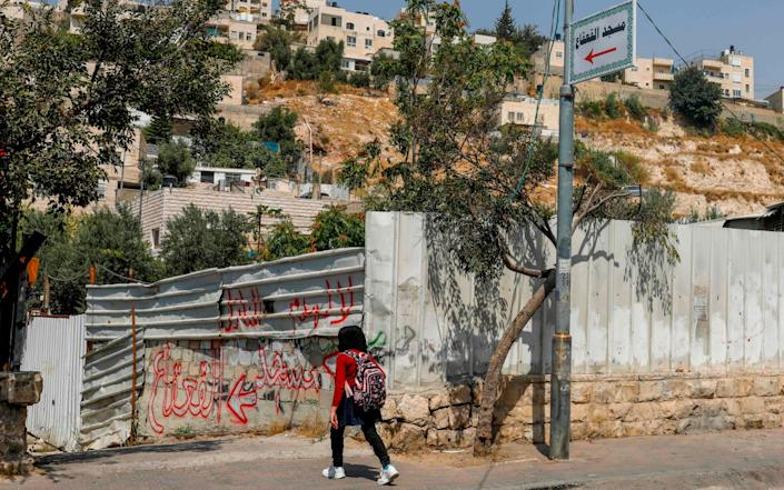 A Palestinian girl walks towards an alley leading to the Qaqaa Bin Amr mosque, in the mostly Arab east Jerusalem neighbourhood of Silwan - AFP