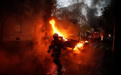 Firemen are at work to extinguish a burning car on the sideline of a demonstration by Yellow vests (Gilets jaunes) protesters against rising oil prices and living costs, on December 1, 2018 in Paris - Credit: ABDULMONAM EASSA/AFP