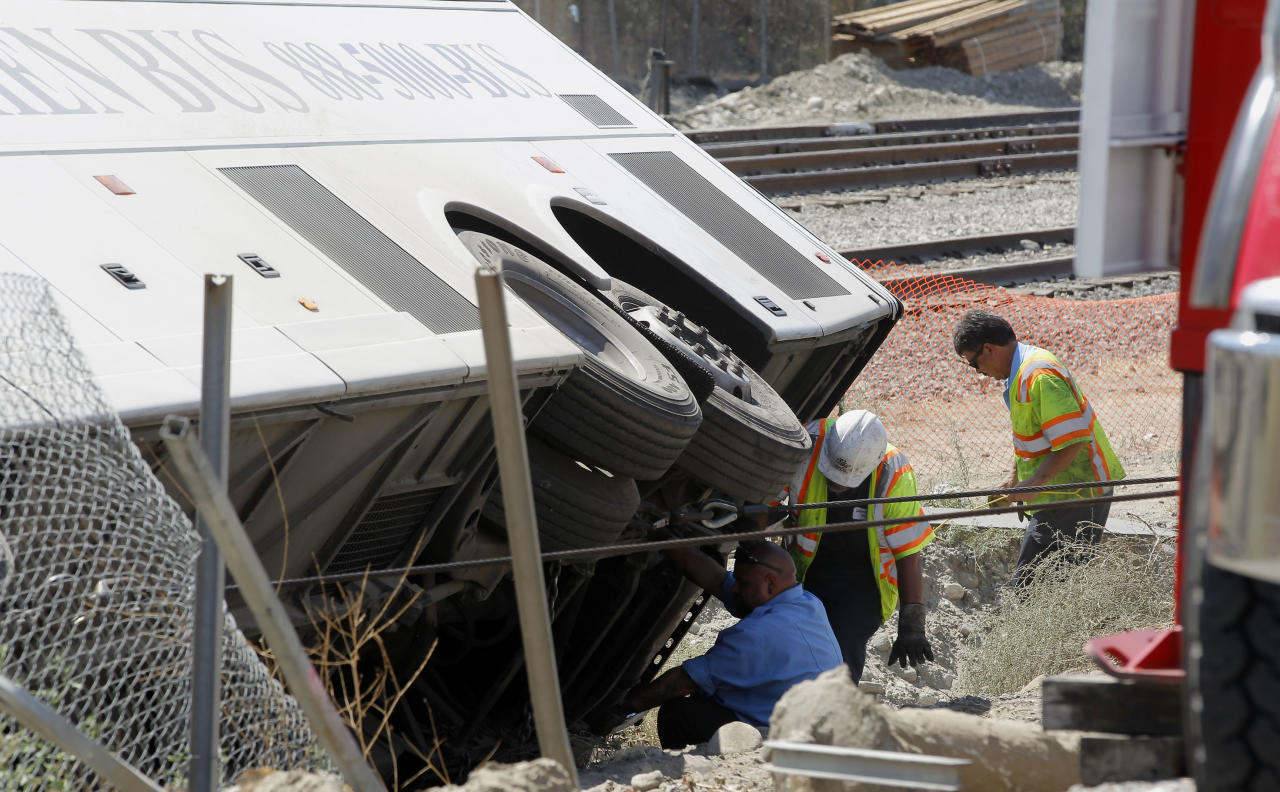 Investigators examine a bus that crashed on Interstate 210 in Irwindale, Calif. on Thursday, Aug 22, 2013. The bus carrying gamblers to a casino overturned on the Southern California freeway injuring more than 50 people on board. The bus went through a chain-link fence off the side of the road and ended up on its side down a dirt embankment between the freeway and railroad tracks. (AP Photo/Nick Ut)