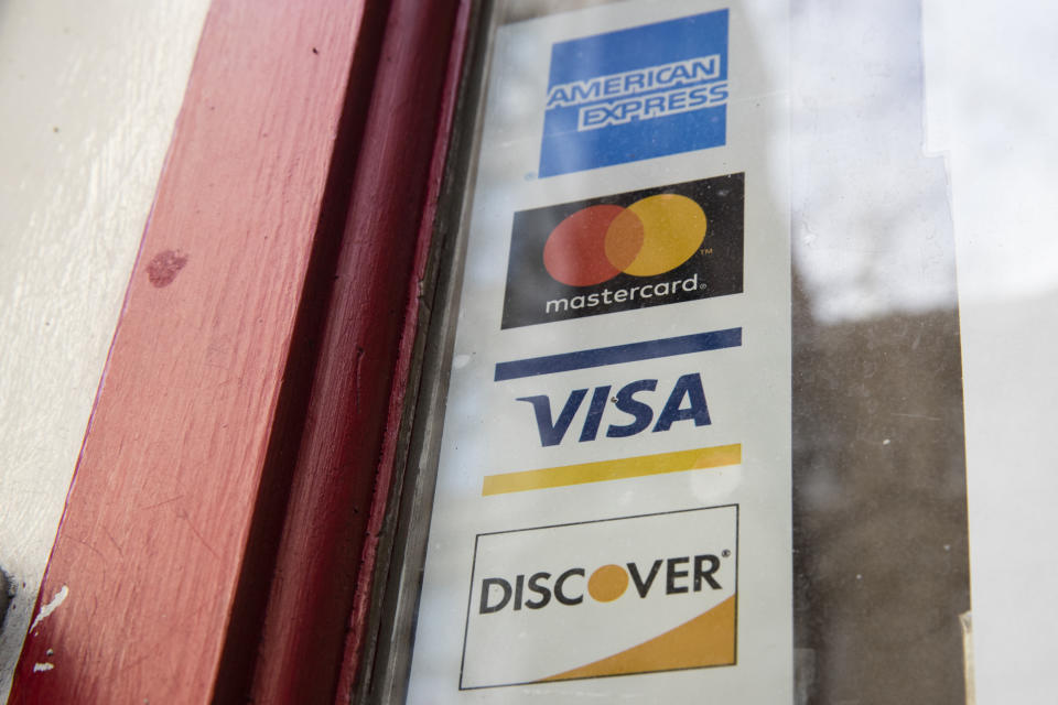 This Nov. 29, 2018, photo shows are credit card logos posted on a store's door in Philadelphia. (AP Photo/Matt Rourke)