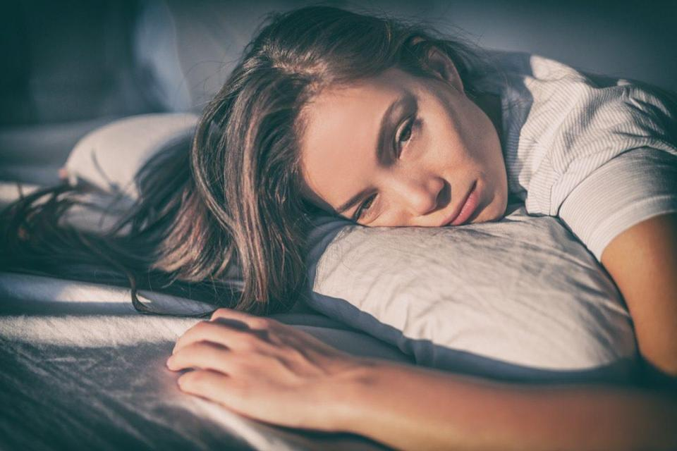 Tired woman lying in bed can't sleep late at night with insomnia