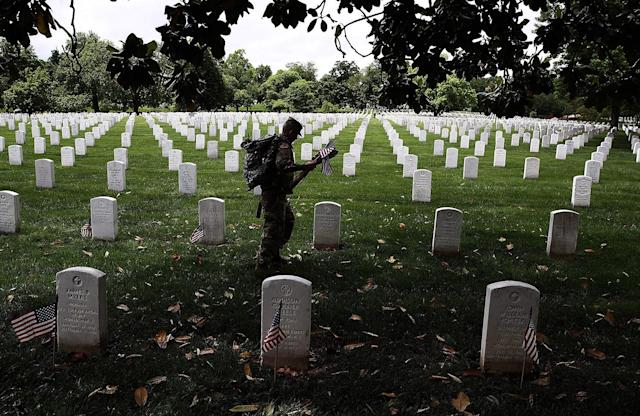 <p>Members of the 3rd U.S. Infantry Regiment place flags at the headstones of U.S. military personnel buried at Arlington National Cemetery, in preparation for Memorial Day May 25, 2017 in Arlington, Virginia. (Photo: Win McNamee/Getty Images) </p>