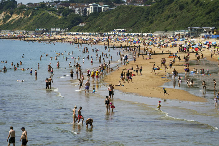 People enjoy the weather on Bournemouth beach in Dorset, England, Monday July 19, 2021. (Steve Parsons/PA via AP)