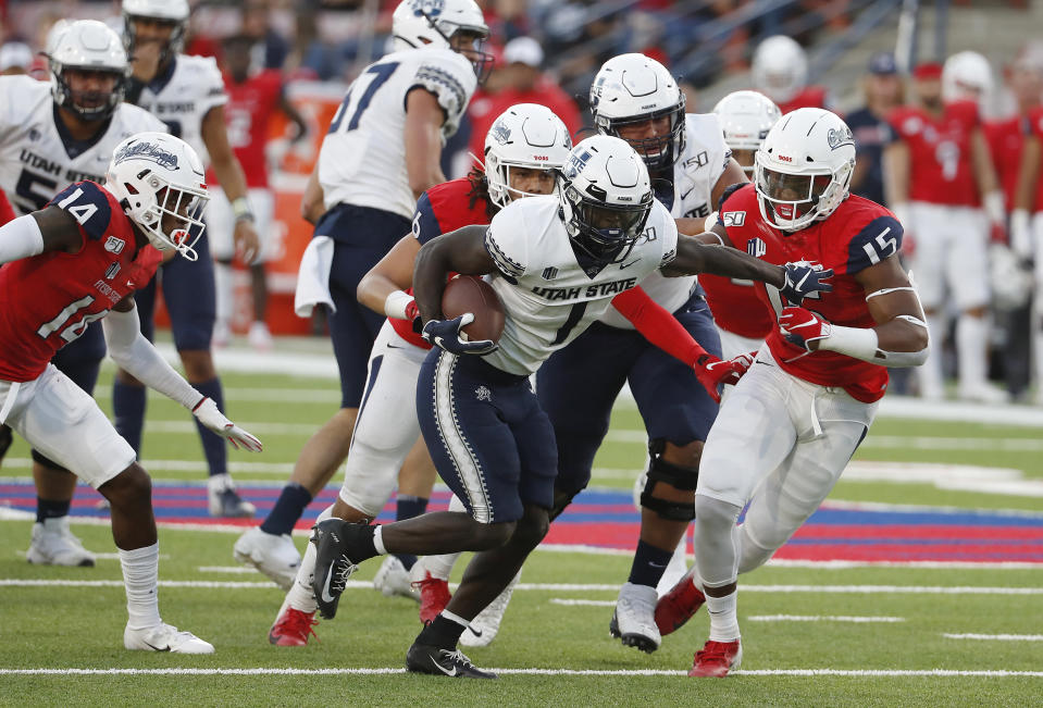 Utah State running back Gerold Bright pushes Fresno State linebacker Arron Mosby out of the way for touchdown during the first half of an NCAA college football game in Fresno, Calif., Saturday, Nov. 9, 2019. (AP Photo/Gary Kazanjian)