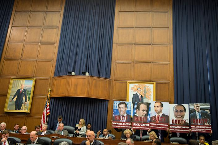 Attendees at a House committee hearing on July 12 hoist posters depicting five men who pleaded guilty to charges brought by Mueller.