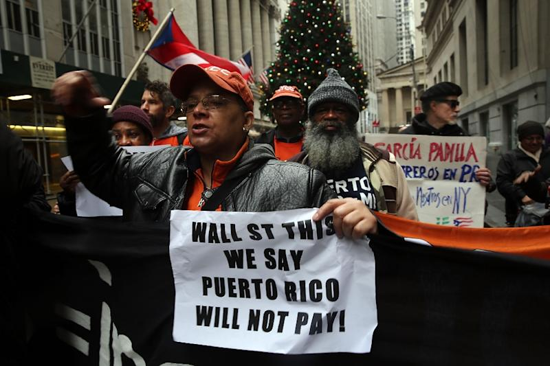 People protest outside of Wall Street to demand that the severely indebted island of Puerto Rico not pay on December 2, 2015 in New York City (AFP Photo/Spencer Platt)