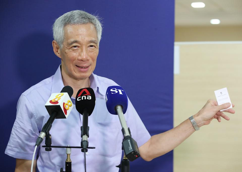Prime Minister Lee Hsien Loong showing members of the media his vaccination card on 8 January 2020. (PHOTO: MCI)