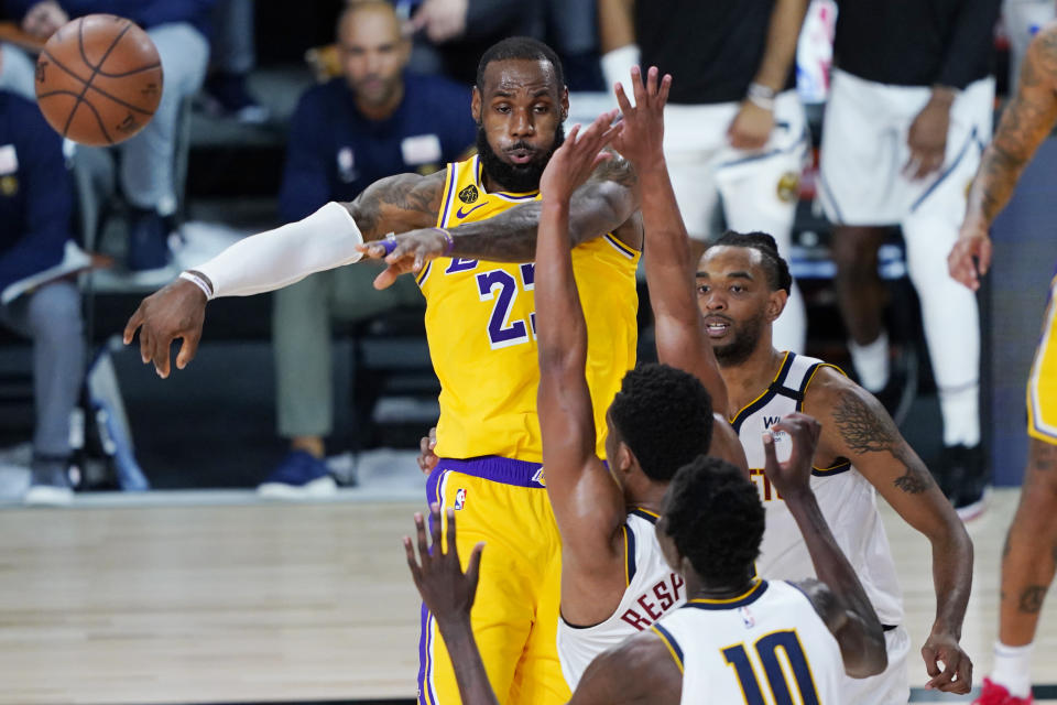 LeBron James passes the ball on the court with Nuggets around him.