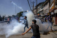 Kashmiri Shiite Muslims throw back tear gas shells fired by Indian police during a religious procession in central Srinagar, Indian controlled Kashmir, Tuesday, Aug. 17, 2021. Police in Indian-controlled Kashmir on Tuesday fired tear gas and warning shots to disperse hundreds of Shiite Muslims, while detaining dozens who attempted to participate in processions marking the Muslim month of Muharram.(AP Photo/Dar Yasin)
