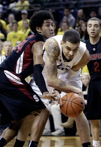 Stanford forward Josh Huestis, left, reaches in to knock the ball away from Oregon center Waverly Austin during the first half of an NCAA college basketball game in Eugene, Ore., Saturday, Feb. 23, 2013. (AP Photo/Don Ryan)