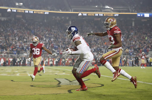 New York Giants wide receiver Odell Beckham Jr., center, scores in front of San Francisco 49ers cornerback Ahkello Witherspoon, right, and defensive back Antone Exum (38) during the second half of an NFL football game in Santa Clara, Calif., Monday, Nov. 12, 2018. (AP Photo/Tony Avelar)