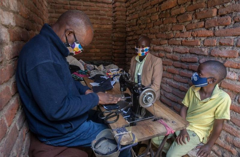 Two masked people look on as a tailor creates face masks.