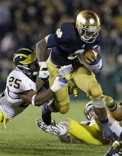 Notre Dame's Theo Riddick (6) runs out of the attempted tackle of Michigan's Kenny Demens (25) during the second half of an NCAA college football game Saturday, Sept. 22, 2012, in South Bend, Ind. No. 11 Notre Dame defeated No. 18 Michigan 13-6. (AP Photo/Darron Cummings)
