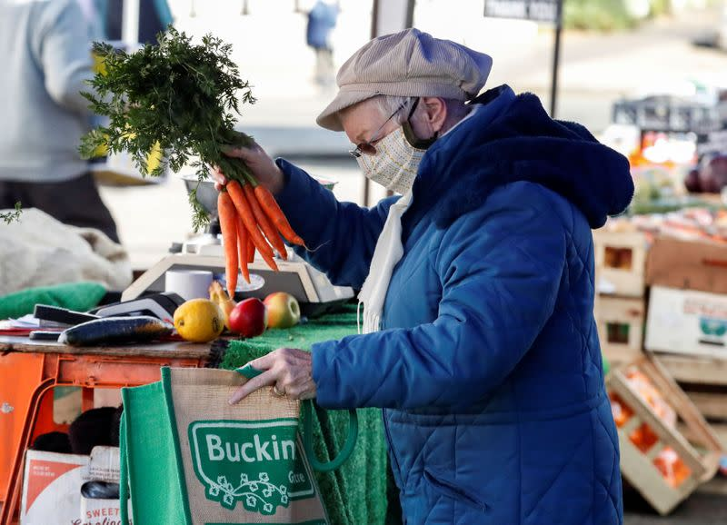 A lady buys carrots from a market stall in Buckingham, Britain
