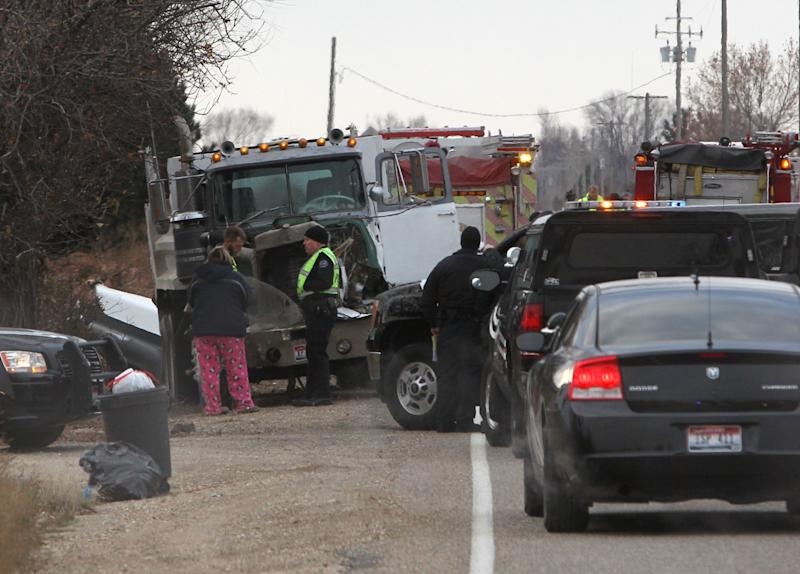 Law enforcement officials respond to the scene of a fatal crash on Thursday, Dec. 5, 2013 in Kuna, Idaho. Authorities say one child has died and five people were injured, including four children, when a dump truck collided with a school bus carrying elementary school students in Kuna, a town about 30 minutes from Boise. Canyon County Sheriff spokeswoman Theresa Baker confirmed the death and said the parents have been notified. Baker says as many as 10 children in the sixth grade or younger were on a bus destined for Crimson Point Elementary School. (AP Photo/The Idaho Statesman, Darin Oswald) LOCAL TV OUT, KTVB 7 OUT THE IDAHO PRESS-TRIBUNE OUT
