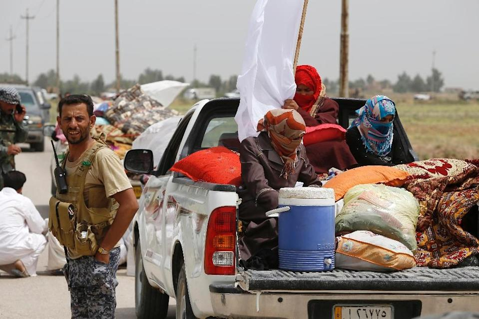 Iraqi pro-government militiamen evacuate people after the liberation from Islamic State militants of the village of Sayed Ghareeb, on June 2, 2015 (AFP Photo/Mohammed Sawaf)