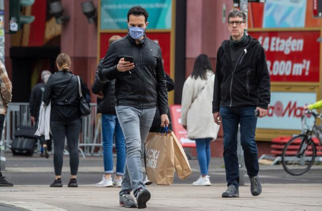 A man wearing a face mask walks out of a shopping centre in Berlin. (John Macdougall/AFP via Getty Images)