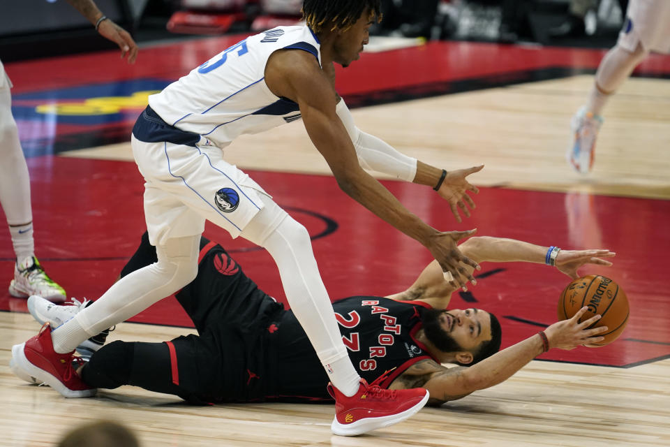 Toronto Raptors guard Fred VanVleet (23) loses the ball as he falls to the floor in front of Dallas Mavericks forward Wes Iwundu (25) during the second half of an NBA basketball game Monday, Jan. 18, 2021, in Tampa, Fla. (AP Photo/Chris O'Meara)