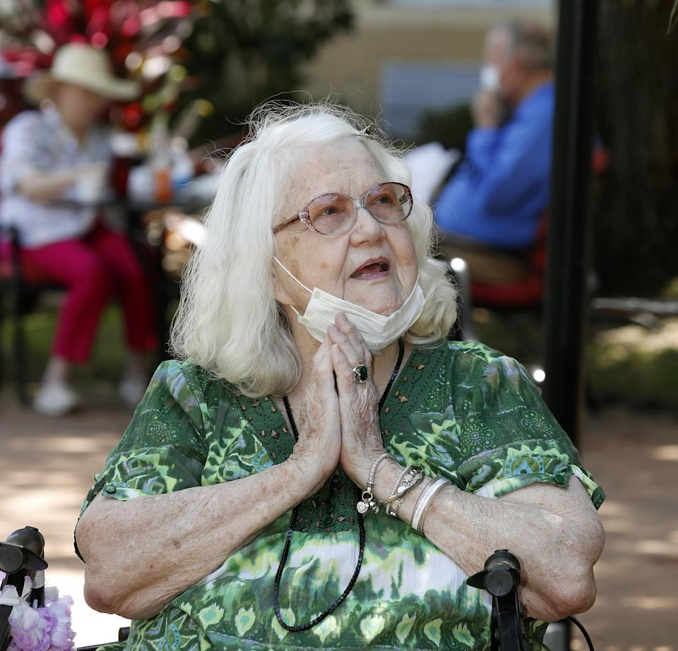 JoAnn Reck, in the courtyard, talks with her husband, Sam Reck, on the balcony at Florida Presbyterian Homes in Lakeland, Florida, in May. When Joann was moved from their apartment into the skilled nursing area of the facility, the couple were separated due to a state mandate closing nursing home visits. However, they would meet three times a week in this distant setting.