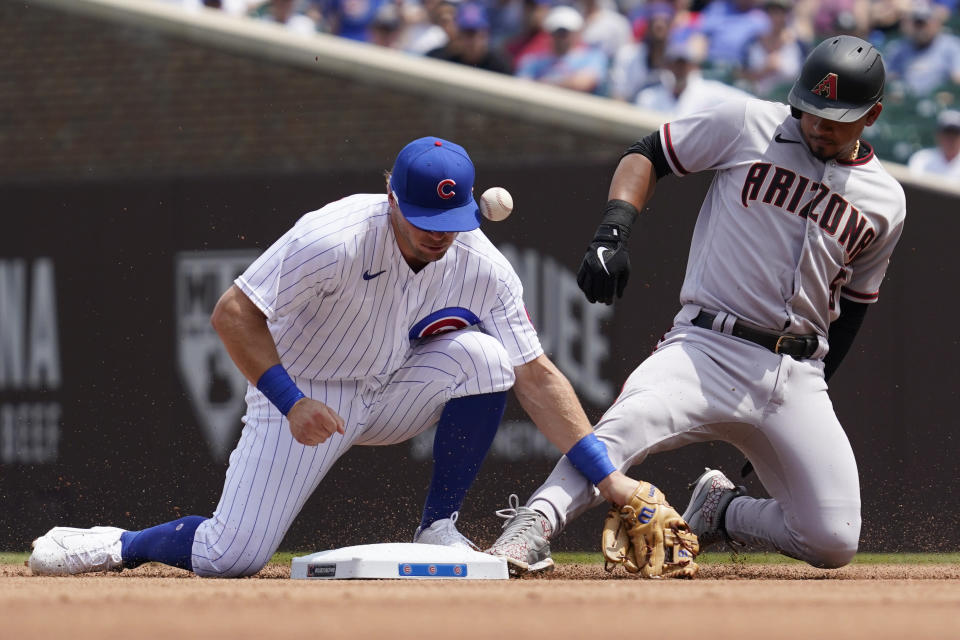 Arizona Diamondbacks' Eduardo Escobar, right, slides safely into second base after hitting a double as Chicago Cubs second baseman Nico Hoerner misses the catch during the first inning of a baseball game in Chicago, Saturday, July 24, 2021. (AP Photo/Nam Y. Huh)