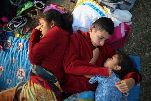 "<p>The Zelaya siblings, from El Salvador, Nayeli, right, Anderson, center, and Daniela, huddle together on a soccer field, at the sports club where Central American migrants traveling with the annual ""Stations of the Cross"" caravan are camped out, in Matias Romero, Oaxaca State, Mexico on April 4, 2018. The children's father Elmer Zelaya, 38, said the family is awaiting temporary transit visas that would allow them to continue to the U.S. border, where they hope to request asylum and join relatives in New York. (Photo: Felix Marquez/AP) </p>"
