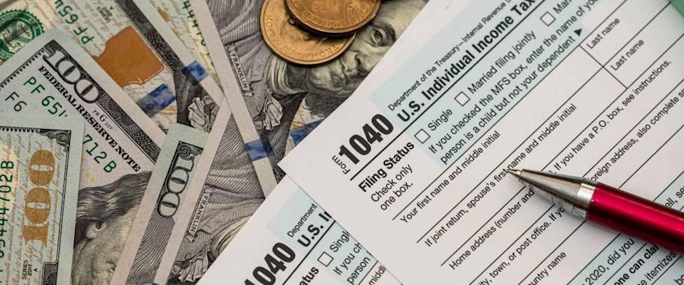 1040 US tax form with pen and dollars on desk. Calculating your tax refund