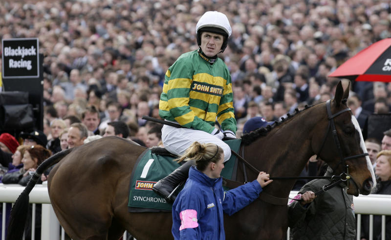 Syncronised with jockey Tony McCoy is led to the start of the Grand National horse race at Aintree Racecourse Liverpool, England, Saturday, April 14, 2012. Synchronised, who won the Cheltenham Gold Cup last month, suffered a fatal injury after falling early in the Aintree race, owner J.P. McManus announced. (AP Photo/Jon Super)
