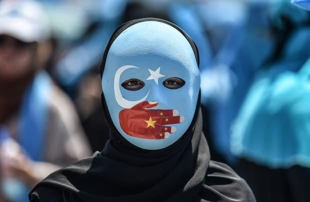A demonstrator wearing a mask painted with the colours of the flag of East Turkestan and a hand bearing the colours of the Chinese flag attends a protest against China's treatment of ethnic Uyghur Muslims in Istanbul on July 5, 2018. (Ozan Kose/AFP/Getty Images - image credit)