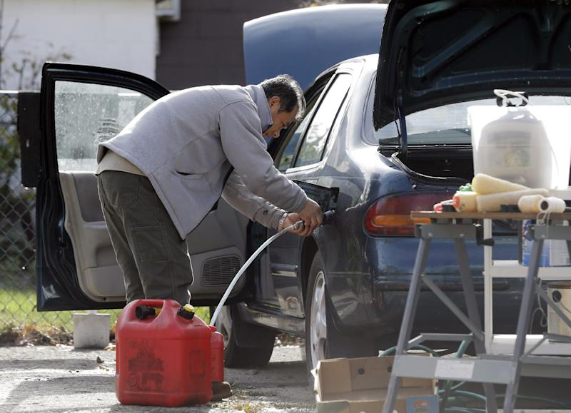 Toshi Ogawa siphons gasoline from his car to use in a generator at his house which is without power in the wake of superstorm Sandy on Thursday, Nov. 1, 2012, in Little Ferry, N.J. New Jersey residents across the state were urged to conserve water. At least 1.7 million customers remained without electricity. (AP Photo/Mike Groll)