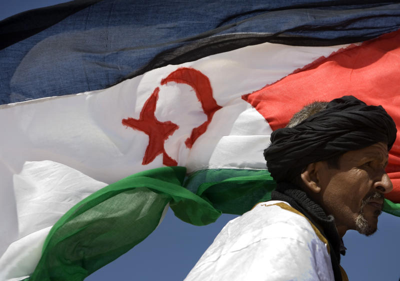 FILE - In this May 19, 2008 file photo, a pro-independence Polisario Front supporter looks on during a military parade as a Western Sahara flag flies in the breeze in the village of Tifariti, to celebrate the 35th anniversary of the Polisario Army. A nasty spat between Algeria and Morocco over the disputed region of Western Sahara has boiled over anew, as Morocco recalled its ambassador, angry protesters tore down an Algerian flag, and a Moroccan magazine called for land grabs. (AP Photo/Daniel Ochoa de Olza, File)