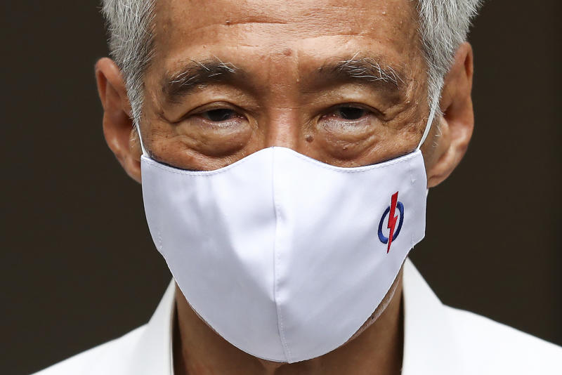 People's Action Party Secretary-General and Singaporean Prime Minister Lee Hsien Loong wears a mask adorned with his party logo as he waits to field questions from the media at a nomination center ahead of the general election in Singapore, Tuesday, June 30, 2020. Campaigning has begun for Singapore's general elections, with the opposition hoping to dent the ruling party's supermajority in parliament with support from Prime Minister Lee's estranged younger brother. (AP Photo/Yong Teck Lim)