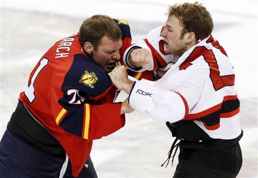 Florida Panthers right wing Krys Barch, left, and New Jersey Devils right wing Cam Janssen fight during the first period of an NHL hockey game, Tuesday, Dec. 13, 2011, in Sunrise, Fla. (AP Photo/Wilfredo Lee)